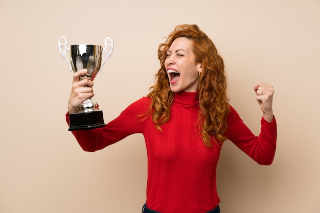 Redhead woman with turtleneck sweater holding a trophy
