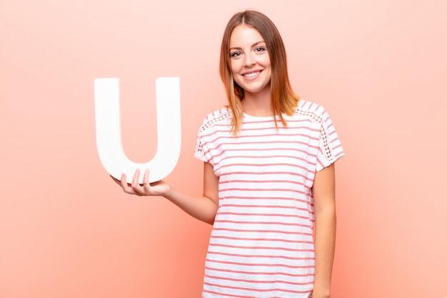 文字uを保持しているtシャツの赤毛の若い女の子