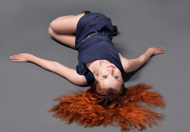 스튜디오에서 포즈를 취하는 검은 드레스에 빨간 머리 소녀
