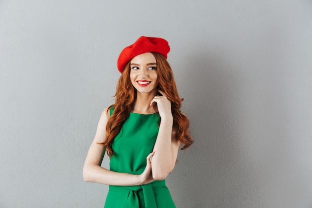 Redhead young happy lady in green dress and red beret