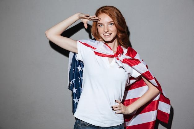 Рыжая молодая леди супергероя с флагом сша.