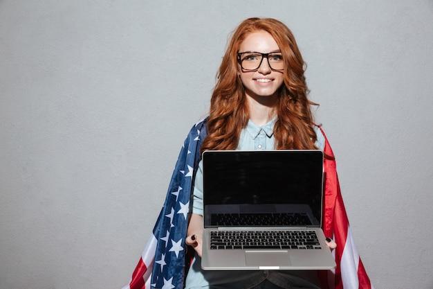 Рыжая девушка с флагом сша показывает дисплей ноутбука