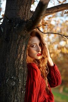 Рыжая молодая женщина в красном свитере гуляет в парке. осенняя красота портрет модной рыжеволосой женщины на закате
