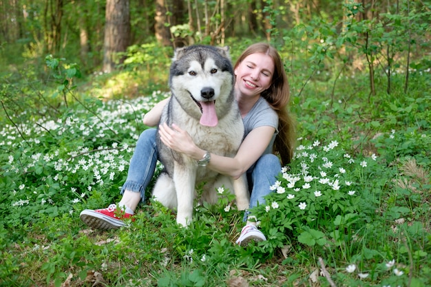 Redhead young woman plays with her dog malamute on a walk in the forest
