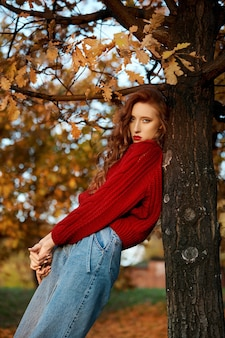Redhead young woman in a red sweater walks in the park. autumn beauty portrait of a fashionable red-haired woman at sunset