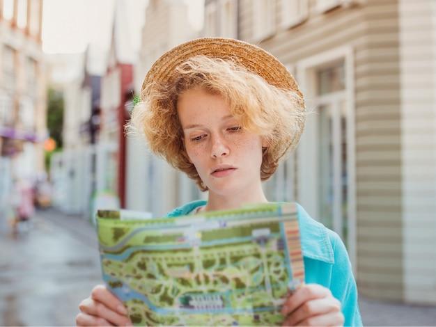 Рыжая молодая женщина путешествует по западной европе и использует бумажную карту в неизвестном городе