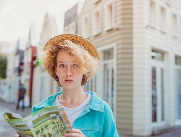 赤毛の若い女性が西ヨーロッパを旅し、未知の町で紙の地図を使用して