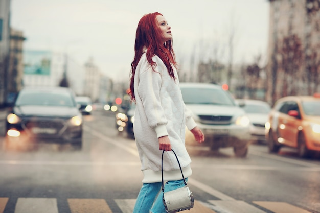 Redhead young woman in a white coat and blue jeans crosses the road at a pedestrian crossing.