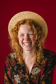 Redhead young woman with hat laughing at camera