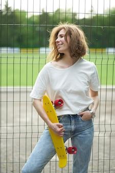 Рыжая молодая женщина со скейтбордом возле забора