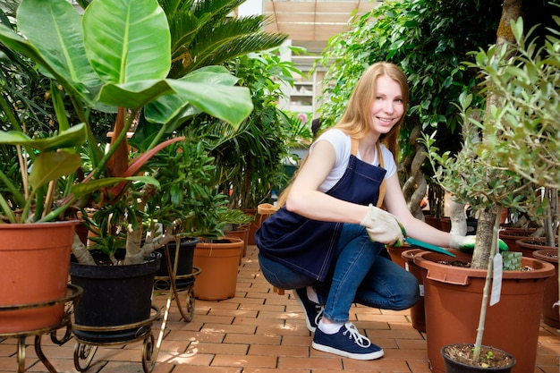 Redhead young woman worker in plant market greenhouse hoeing plants and smiling