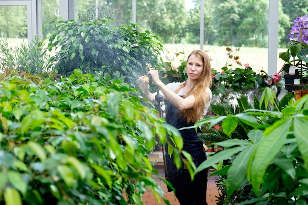 Redhead young woman worker in plant market greenhouse pouring plants