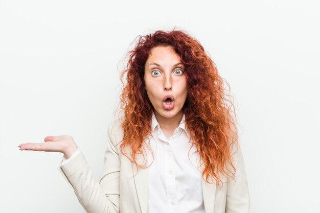 Молодая естественная бизнес-леди redhead против белой стены впечатлила держать пустое пространство на ладони.
