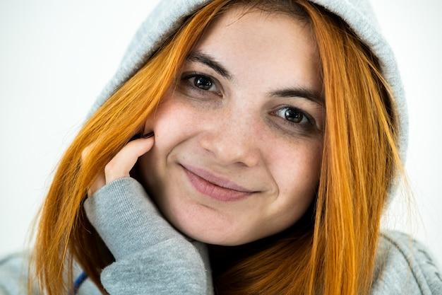 Закройте вверх по портрету счастливой усмехаясь молодой женщины redhead нося теплый пуловер с капюшоном.