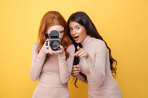 Жизнерадостная молодая африканская женщина указывая пока фотографировать дамы redhead