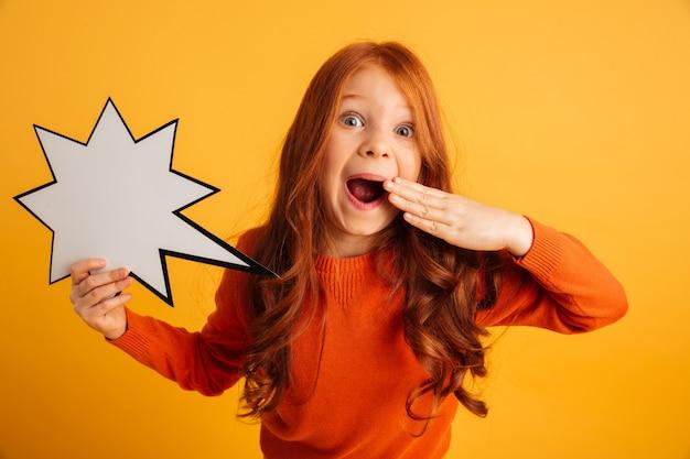 Сотрясенная маленькая девушка redhead держа пузырь речи.