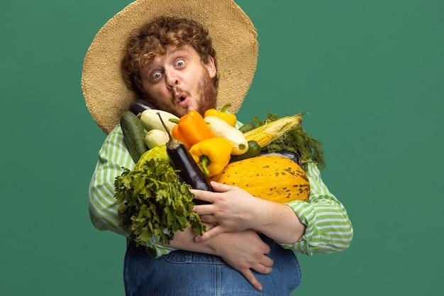 빨간 머리 수염 난 남자, 녹색 스튜디오 벽에 고립 된 야채 수확 농부.