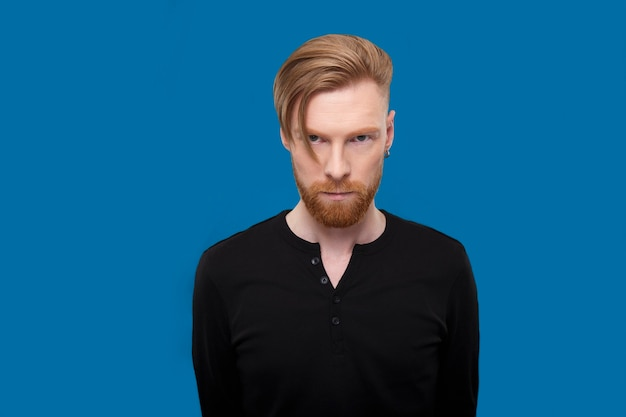 Redheaded bearded man, posing frontal in studio, looking seriously