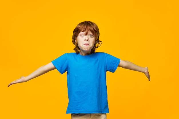 赤毛の少年青いtシャツ黄色の背景そばかすは驚きに両手を肩にすくめる