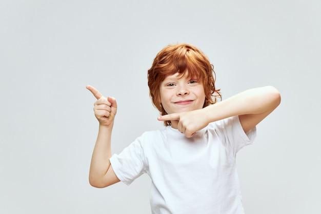 孤立したtシャツを着て笑って赤毛の少年