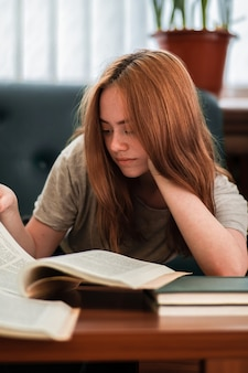 Redheaded girl with interested facial expression reading a book in public library.