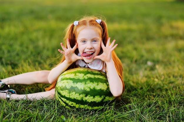 Redheaded girl with watermelon grimaces and smiles sitting on the grass in the park
