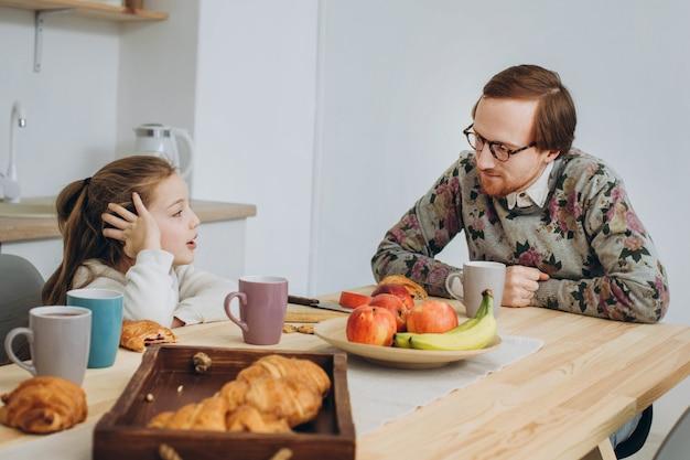 빨간 머리 hipster 아빠와 딸이 함께 부엌에서 아침을 먹고.
