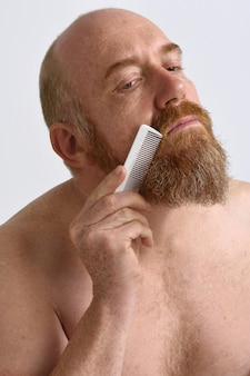Redheaded man combing his beard on white background
