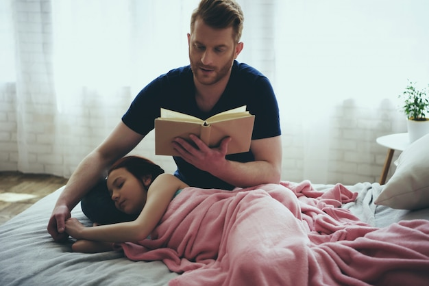 Redheaded single father reads book while daughter sleeps.