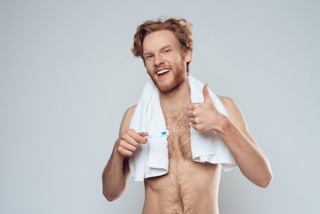 Redheaded smiling man with toothbrush is showing thumbs up.