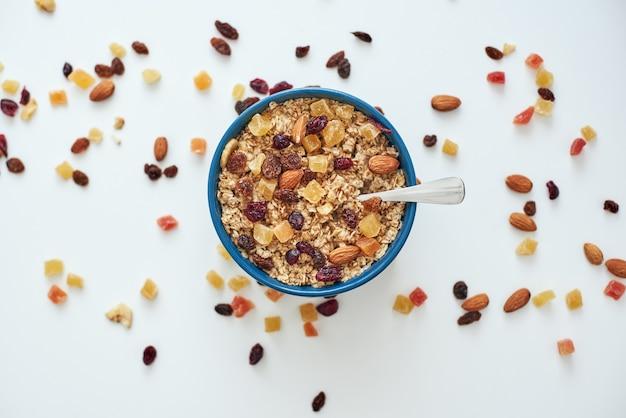 칼로리를 줄이십시오. 건강하고 유용한 아침 식사, 그릇에 담긴 귀리, 흰색 배경에 격리된 마른 과일의 최고 전망. 아침에 건강한 간식이나 아침 식사. 뮤즐리의 금속 숟가락