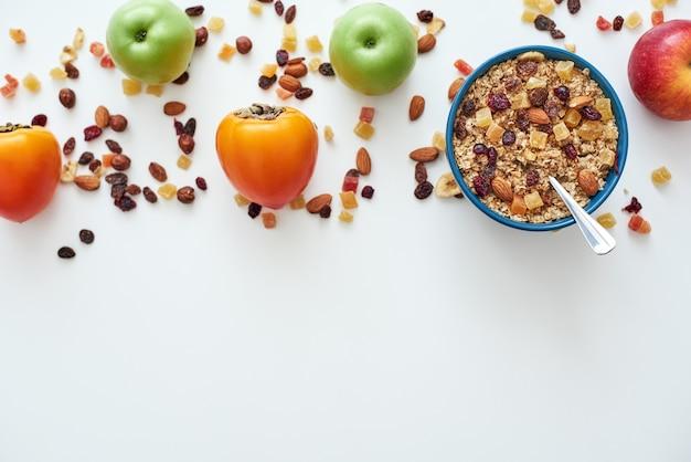 呼び出しを減らします。健康的で便利な朝食、ボウルにオーツ麦、白い背景で隔離の果物の上面図。朝のヘルシーなおやつや朝食。ミューズリーの金属スプーン