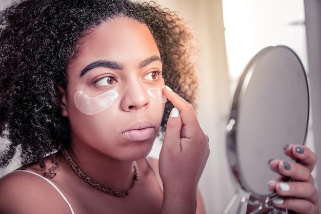 Уменьшение кругов под глазами. внимательная смуглая женщина проверяет действие повязок на глаза для уменьшения синяков под глазами
