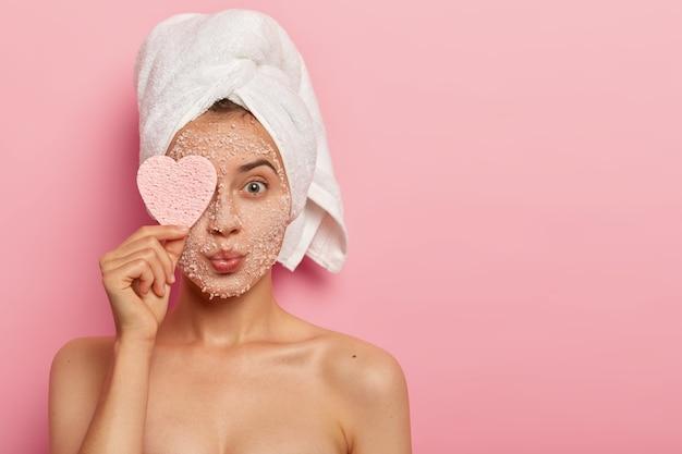 모공 감소 및 클렌징 컨셉. 매력적인 여성은 얼굴에 해염 마스크를 바르고, 에스테틱에서 고급스러운 느낌을 받고, 하트 모양의 스펀지로 눈을 가리고, 안색을 가꾸어줍니다.