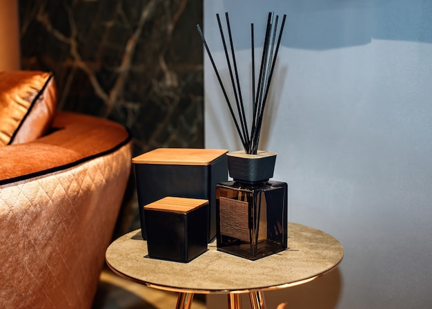 Reed diffuser and decorative boxes on the stylish table in contemporary style home interior