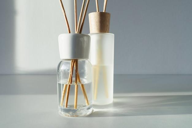 テーブルのリードディフューザー。花の香りのあるアロマスティック。商業フラットレイアウト、正面図。アロマセラピーの香り。コピースペース