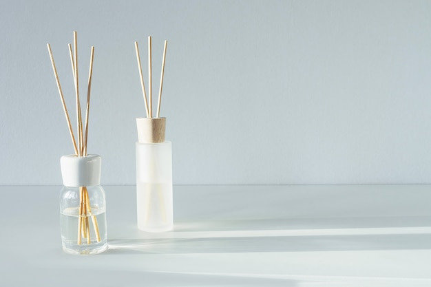 Reed diffusers on table. aromatic sticks with floral odor. commercial flat lay, front view. aromatherapy fragrance. copy space
