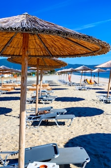 Reed umbrellas and sun beds at the empty beach