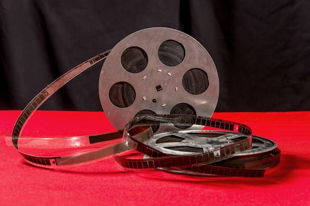 Reel of film  on a red table with black surface