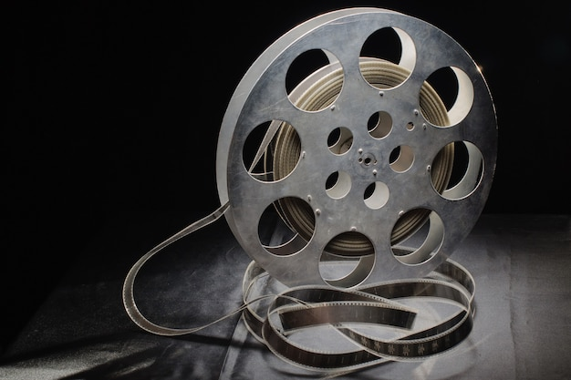 Reel of film standing on a black table with black surface