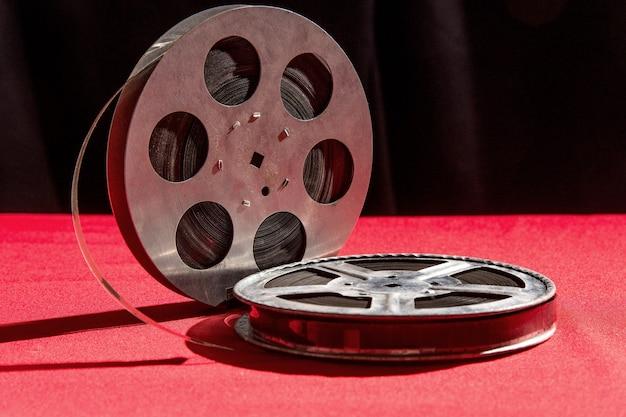 黒い表面の赤いテーブルの上のフィルムのリール