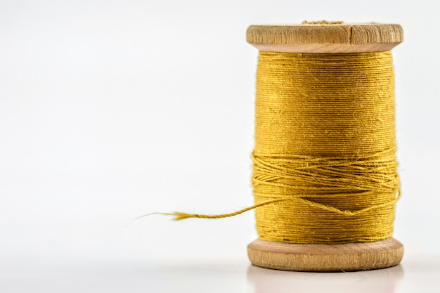 Reel or spool of yellow sewing thread isolated on white. shallow depth of field. close-up macro shot.