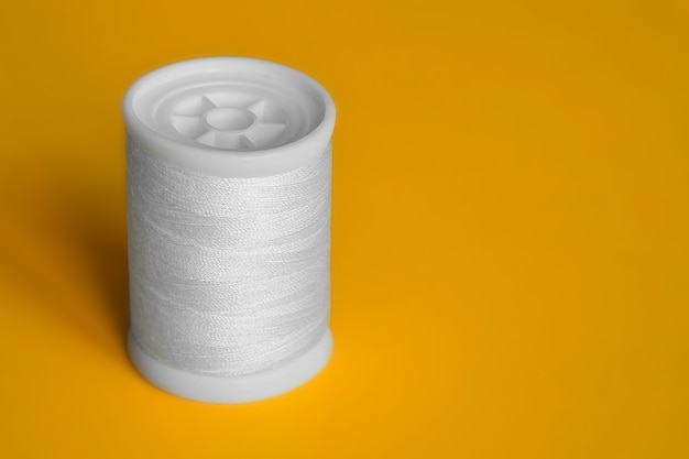 Reel of white sewing threads on bright yellow background. copy space, close-up.
