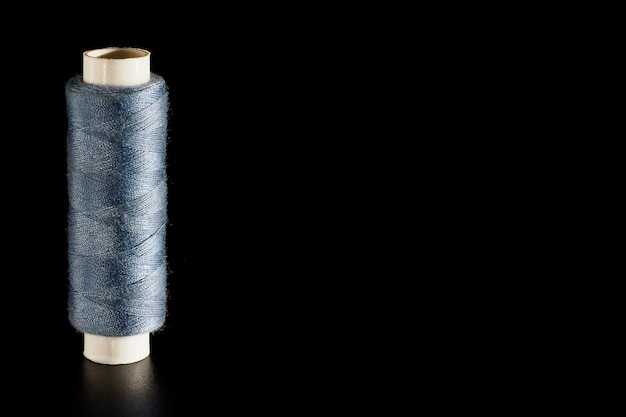 Reel with gray sewing silk threads isolated on a black background, close-up, copyspace.