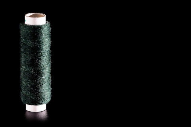 Reel with green sewing silk threads isolated on a black background, close-up, copy space.
