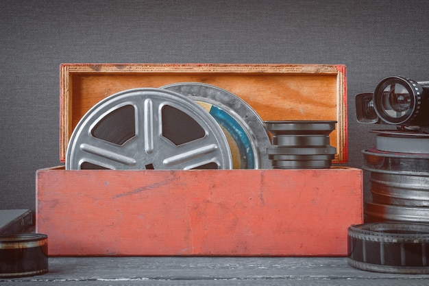 Reels with films in a wooden box, lens and an old movie camera