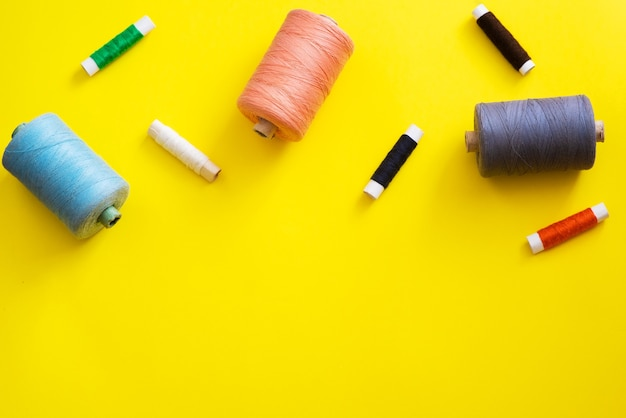 Reels with threads of different colors and sizes on a bright, colorful background. flat lay. place for text, copyspace