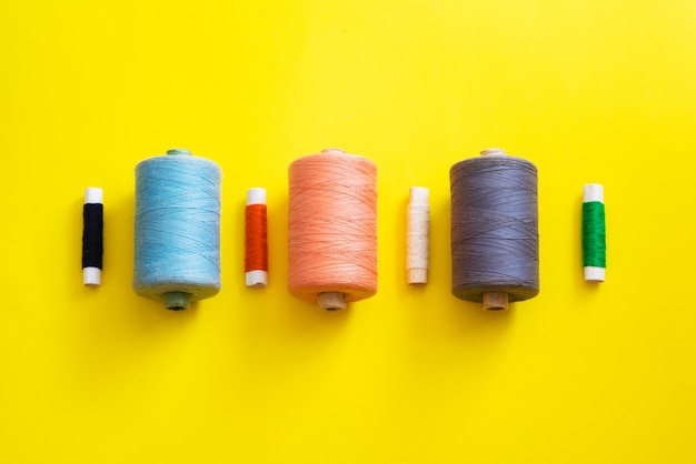 Reels with threads of different colors and sizes on a bright, colorful background. flat lay