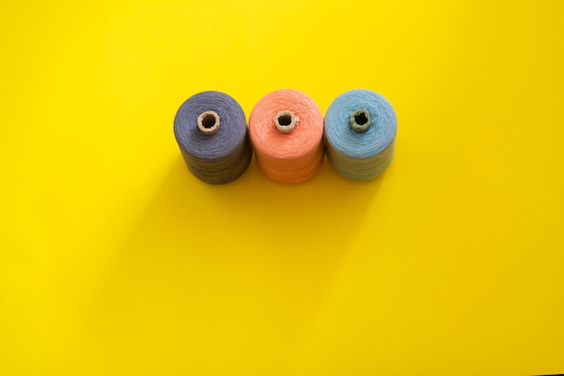 밝고 화려한 배경에 다양한 색상과 크기의 스레드가 있는 릴. 플랫 레이. 텍스트, copyspace에 대 한 장소