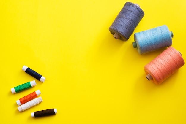 Катушки с нитками разных цветов и размеров на ярком, красочном фоне. плоская планировка. место для текста, copyspace